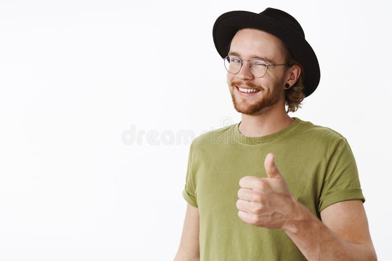 Trevlig arbetsman, som det Tillfredsställd lycklig och vänlig charmig skäggig man i hatt och exponeringsglas som blinkar förtjust fotografering för bildbyråer