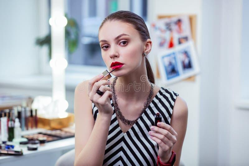 Trevlig attraktiv ung kvinna som applicerar hennes makeup royaltyfri bild
