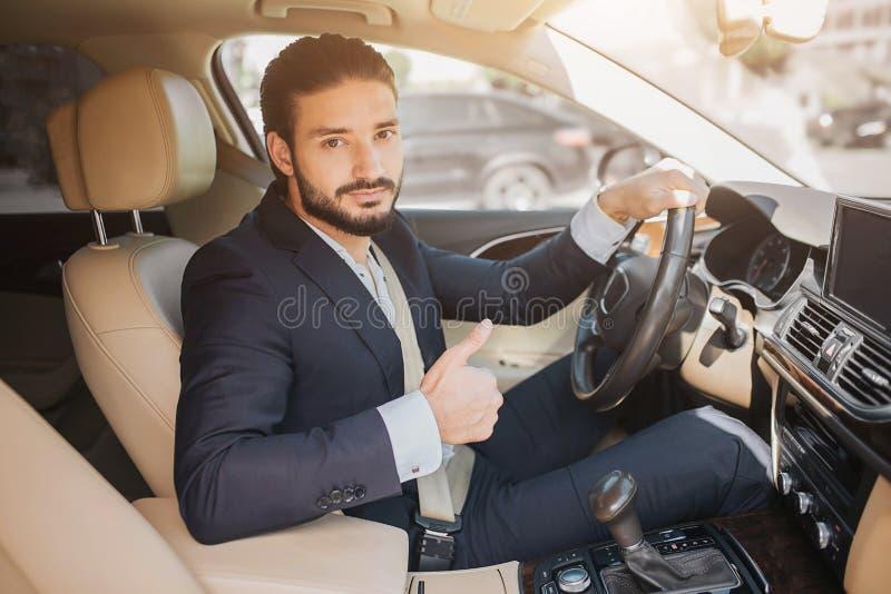 Trevlig bild av den unga affärsmannen som sitter i lyxig bil och rymmer upp den stora tummen Han rymmer en hand på styrninghjulet arkivbild