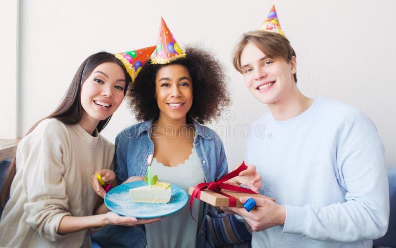 Trevlig bild av en födelsedagflicka och hennes vänner Den asiatiska flickan har ett stycke av kakan Grabben rymmer en gåva i hans arkivfoton