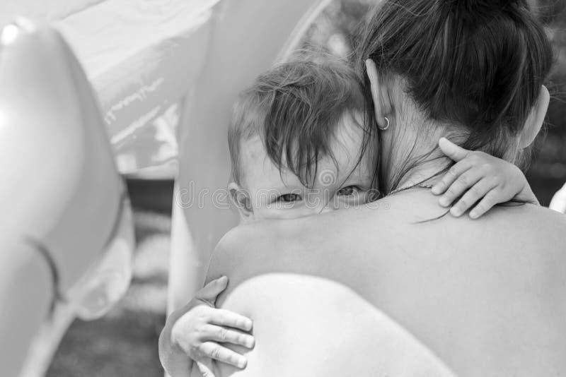 Trevlig bild av en ung uppriven pojke som kelar hans mum barnet ser ut ur moderns skuldra royaltyfria foton