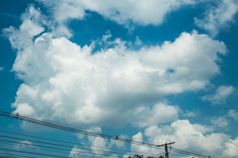 Trevlig blå himmel fördunklar dag med trådar och elektricitetspolen arkivfoton