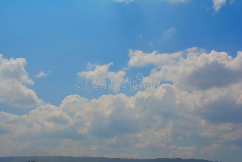 Trevlig blå himmel på en solig dag med en vägg av moln och ett berg på botten royaltyfri bild