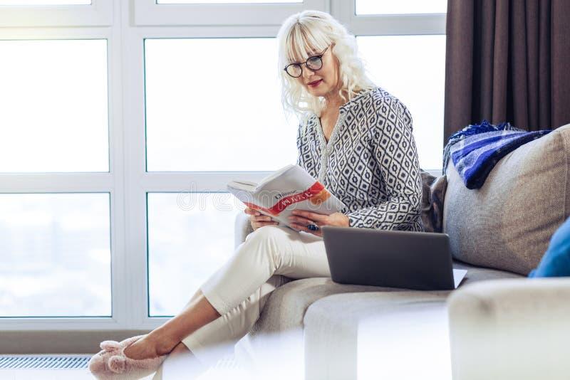 Trevlig blond kvinna som läser en intressant bok royaltyfri foto