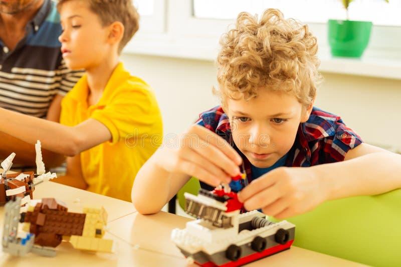 Trevlig blond pojke som spelar med en leksakbehållare fotografering för bildbyråer