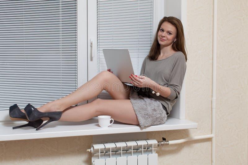 Trevlig blondin på ett fönster med bärbara datorn arkivbild