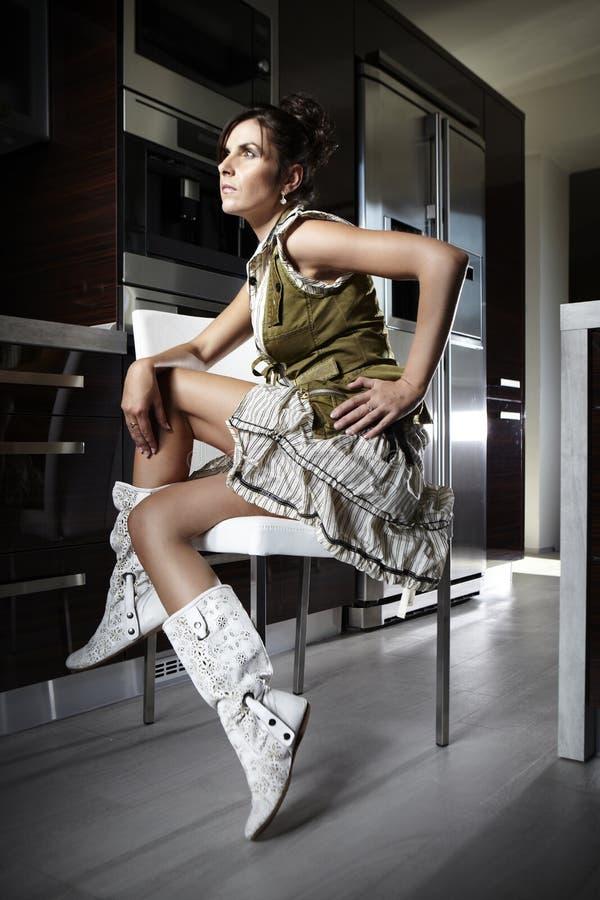 Trevlig brunete sittin i kök arkivfoton