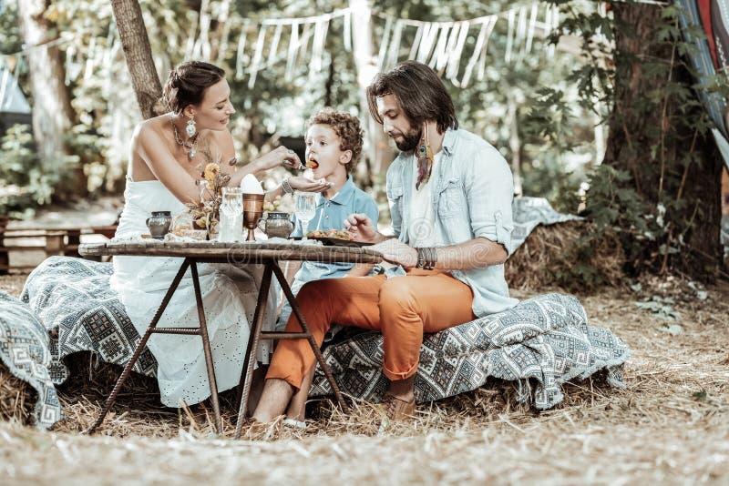 Trevlig familj som har en matställe i trädgården royaltyfria foton