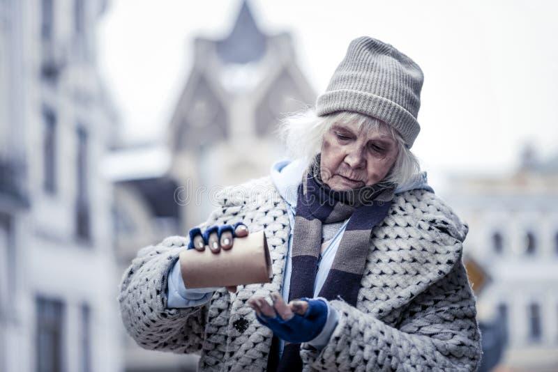 Trevlig fattig kvinna som bläddrar över ett pappers- exponeringsglas fotografering för bildbyråer