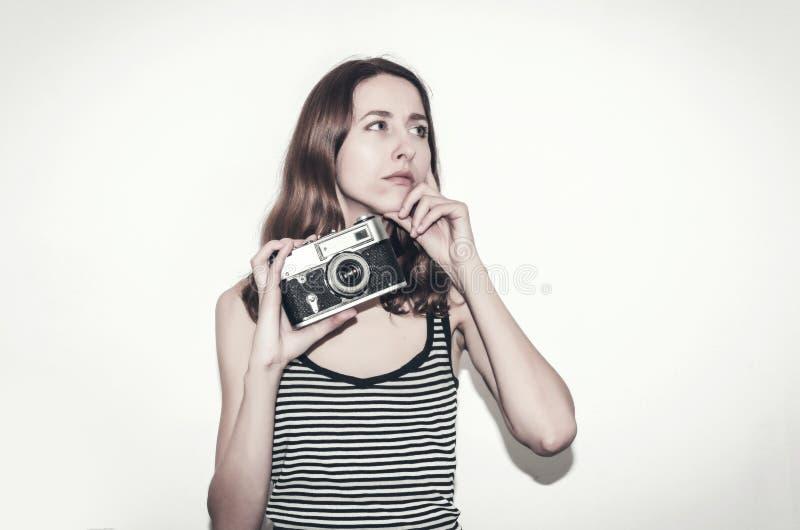 Trevlig flicka i en randig t-skjorta med en tappningkamera i hennes händer Fotografera folk royaltyfri foto