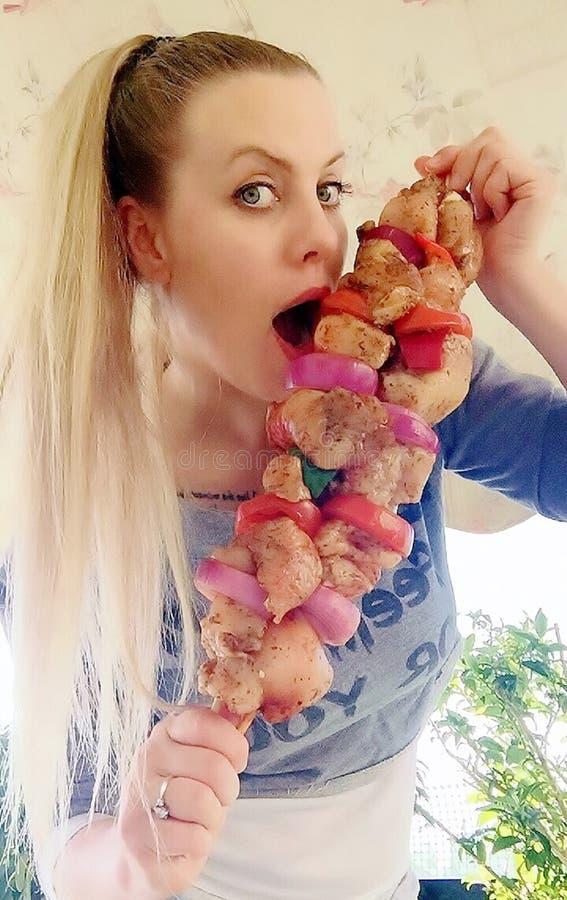 Trevlig flicka med stora kebaber av fegt kött av löken, peppar och olika kryddor arkivfoto