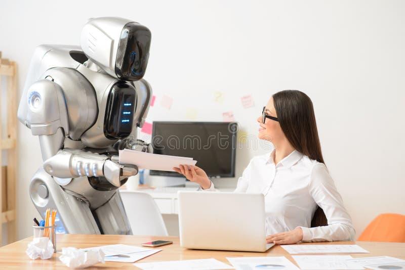 Trevlig flicka och robot som arbetar i kontoret royaltyfri foto