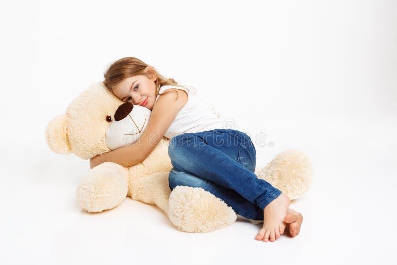 Trevlig flicka som ligger på golv med leksakbjörnen som kramar det royaltyfria foton