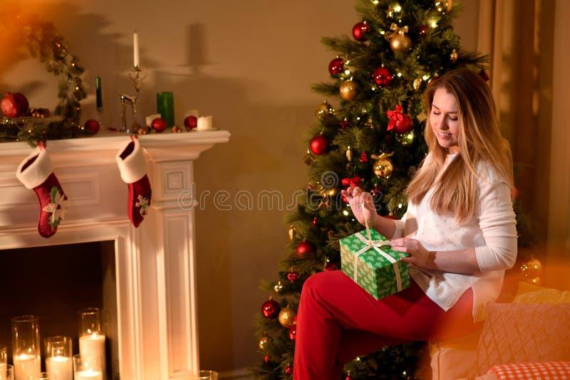 Trevlig flicka som packar upp ett sammanträde för julgåva royaltyfri bild