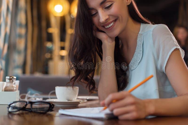 Trevlig fundera kvinna som ner skriver dagordningen royaltyfri bild