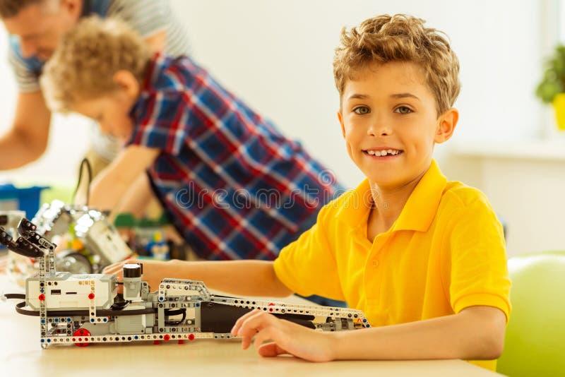 Trevlig glad pojke som visar dig hans arbete royaltyfri bild