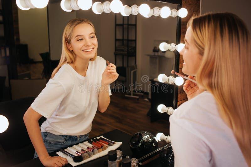 Trevlig gladlynt blick för ung kvinna i spegel i skönhetrum och leende Hon rymmer borsten för ögonskuggor arkivfoton