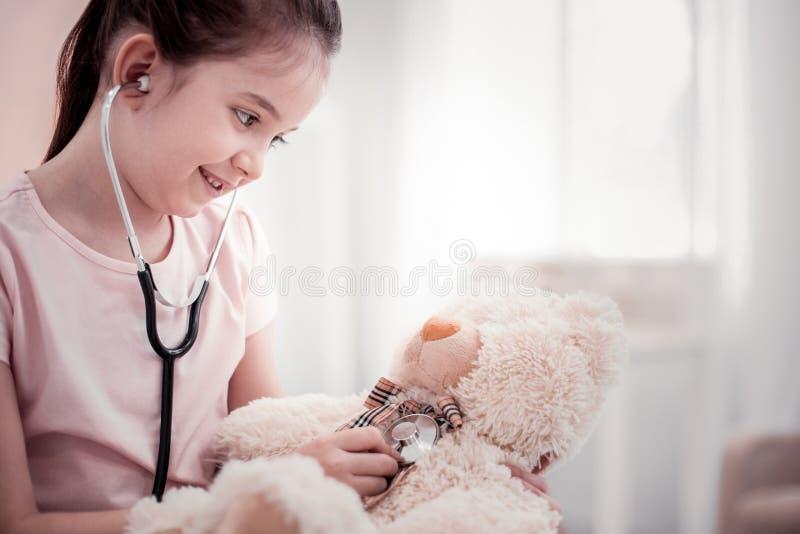 Trevlig gladlynt flicka som behandlar hennes fluffiga björn arkivbild