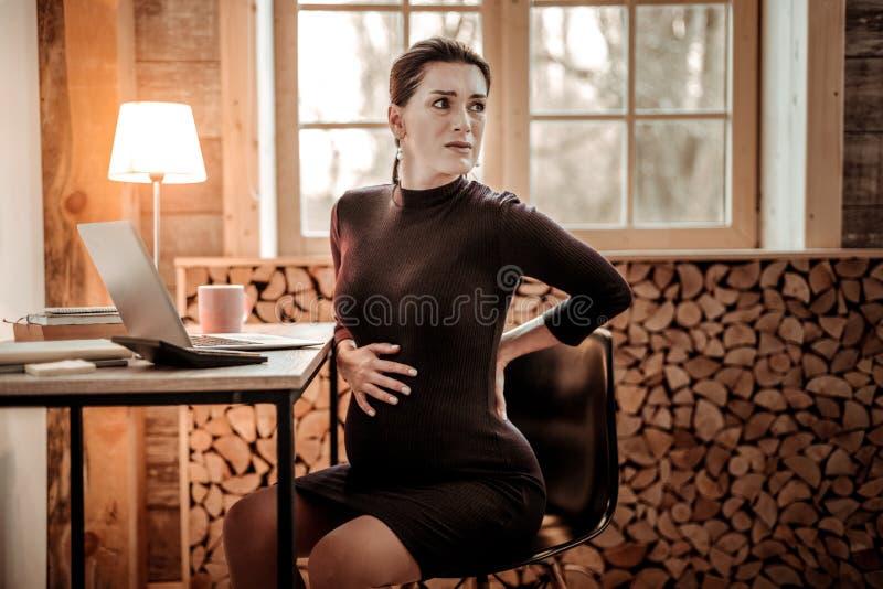 Trevlig gravid kvinna som känner början av arbete royaltyfri foto
