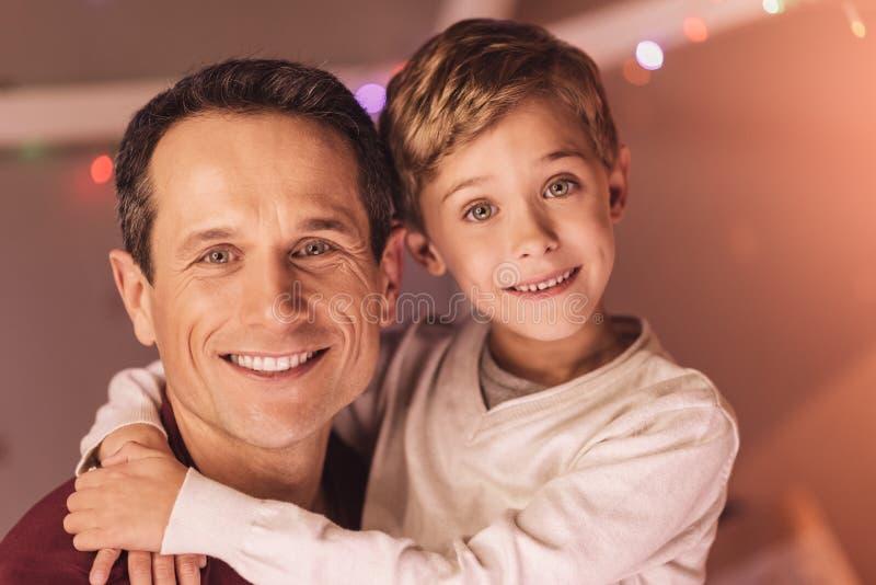 Trevlig gullig pojke som kramar hans fader royaltyfri fotografi