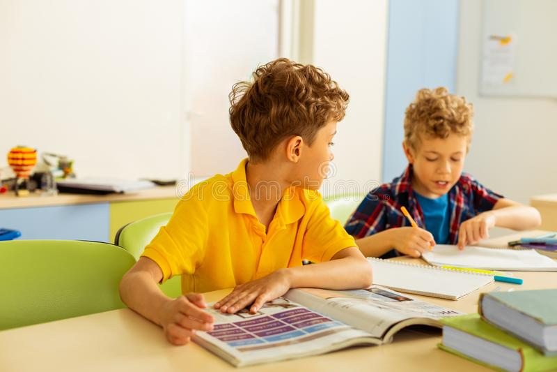 Trevlig gullig pojke som talar med hans klasskompis royaltyfri foto