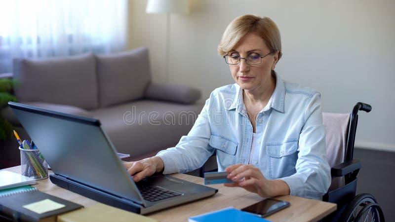 Trevlig hög kvinna i nummer för rullstolmaskinskrivningkort på bärbara datorn som betalar räkningar arkivfoto