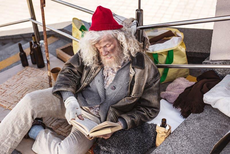 Trevlig hemlös man som läser en bok arkivbilder