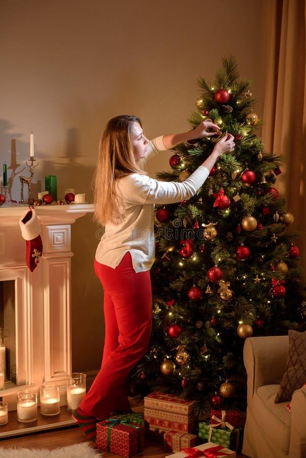 Trevlig kvinna som försiktigt dekorerar ett julträd arkivbilder