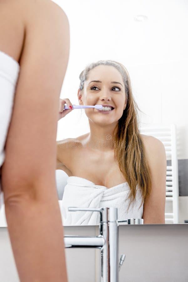 Trevlig kvinna som gör ren hennes tänder arkivbilder