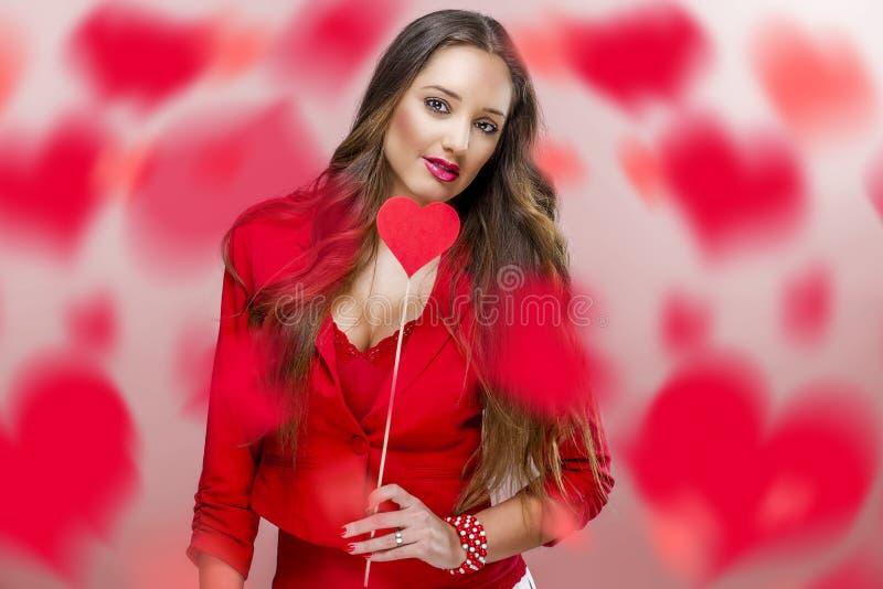 Trevlig kvinna som rymmer röd hjärta arkivfoton