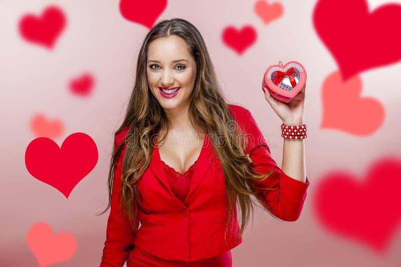 Trevlig kvinna som rymmer röd hjärta royaltyfria foton