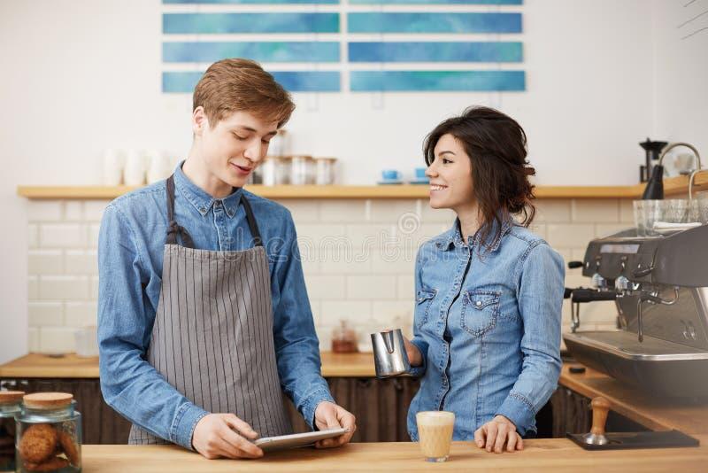 Trevlig kvinnlig barista som gör raf-kaffe som glatt ler och att se lyckligt arkivfoton