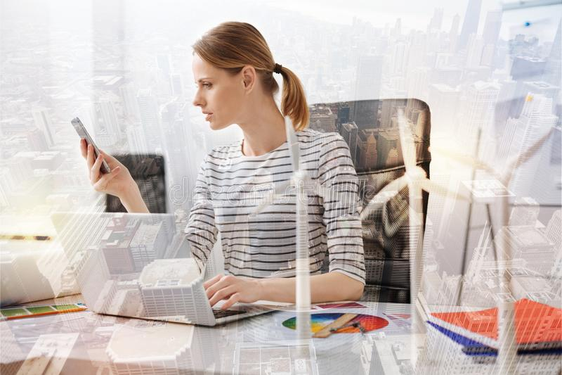 Trevlig kvinnlig ecotekniker som kontrollerar hennes meddelanden arkivfoto