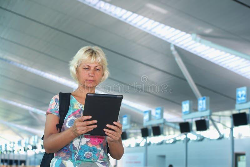 Trevlig kvinnlig med en ryggsäck och en minnestavlaPC royaltyfri bild