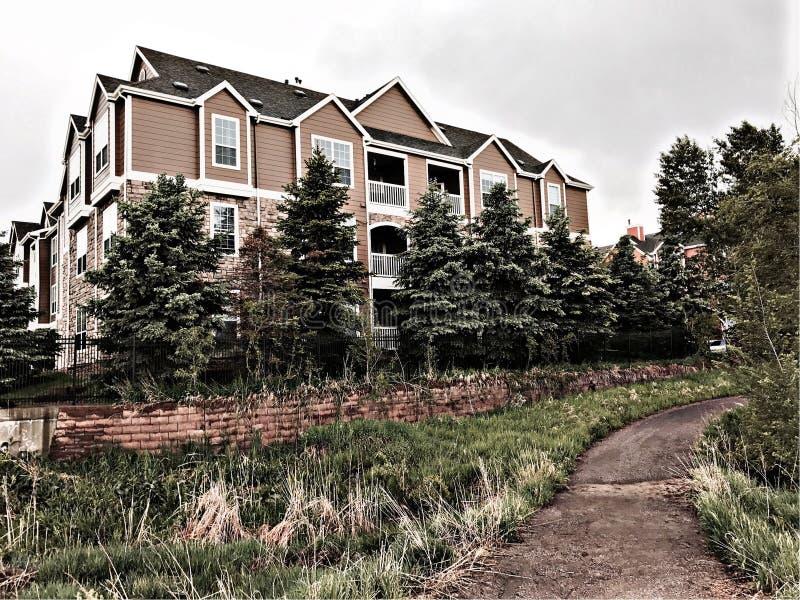 Trevlig lägenhetskomplex med en trädlinje royaltyfri foto