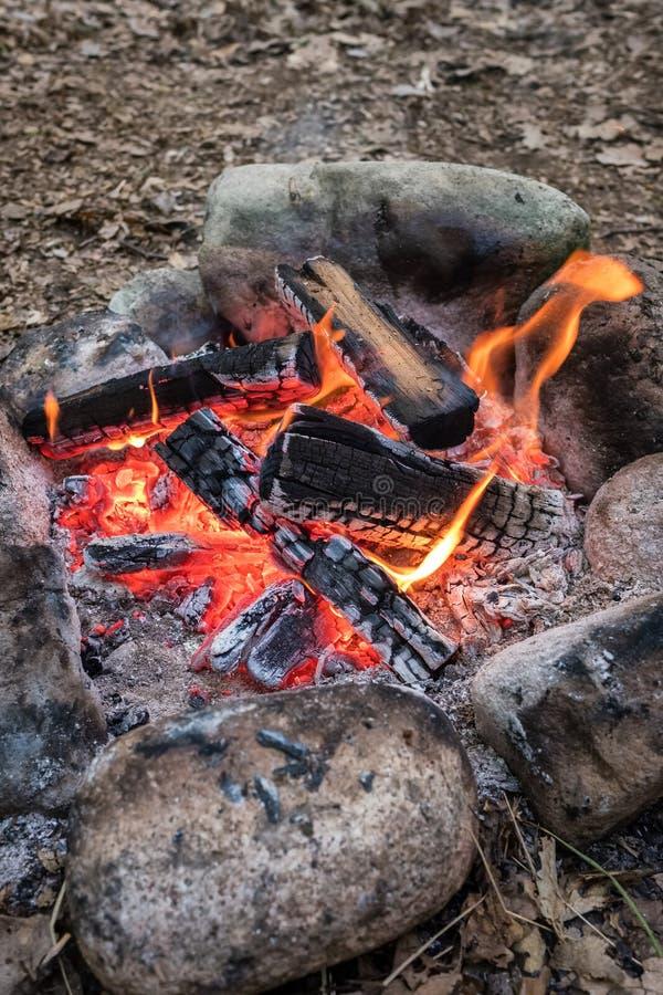Trevlig lägereld i en brandgrop på en campingplats arkivfoto