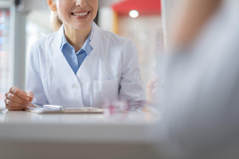 Trevlig le doktor som talar till hennes lilla patient royaltyfri foto