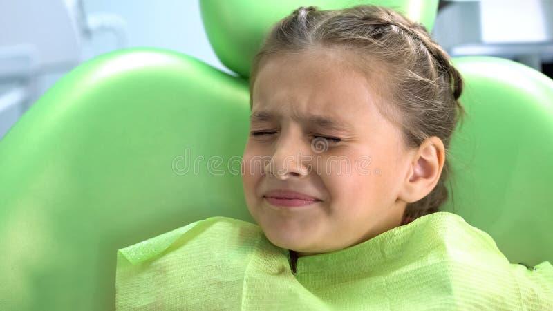 Trevlig liten flicka som är rädd av den rutinmässiga tandläkareundersökningen, hygien av det muntliga hålet royaltyfri fotografi