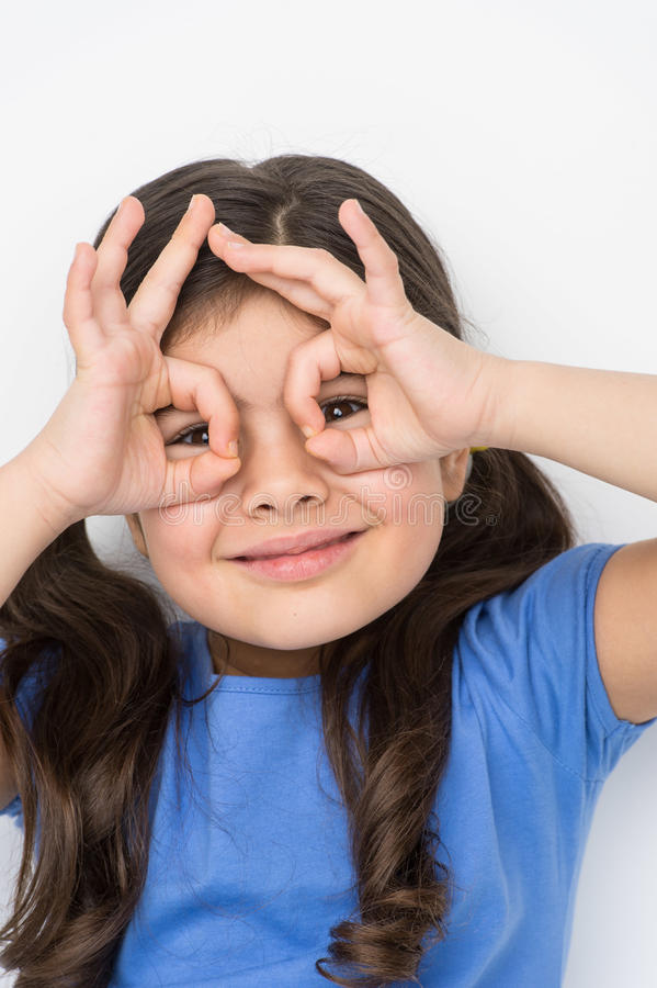 Trevlig liten flicka som gör en gest och spelar royaltyfria foton