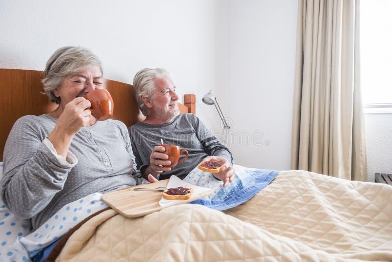 Trevlig lycklig morgon hemma som gör frukosten på säng med många leenden och skratt för att gifta sig caucasian par för vuxen sen royaltyfri foto