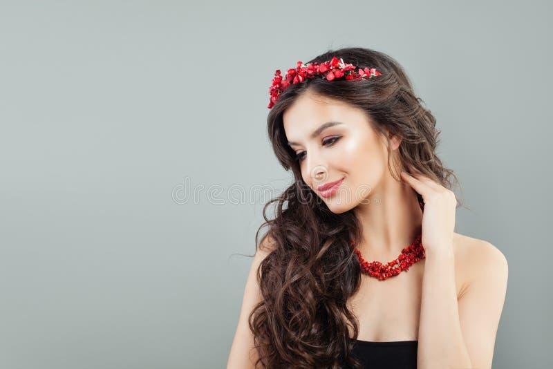 Trevlig modellkvinna med långa bruna hår och korallsmycken royaltyfri foto