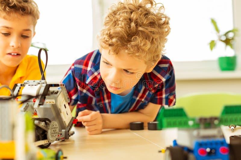 Trevlig nyfiken pojke som ser roboten royaltyfri fotografi