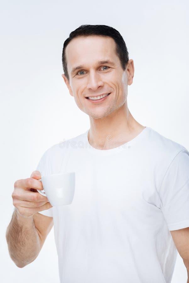 Trevlig positiv man som tycker om hans kaffe royaltyfri fotografi