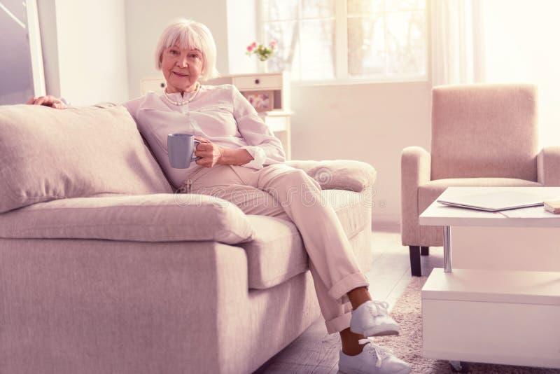 Trevlig positiv pensionär som bär ljus trendig kläder arkivfoton