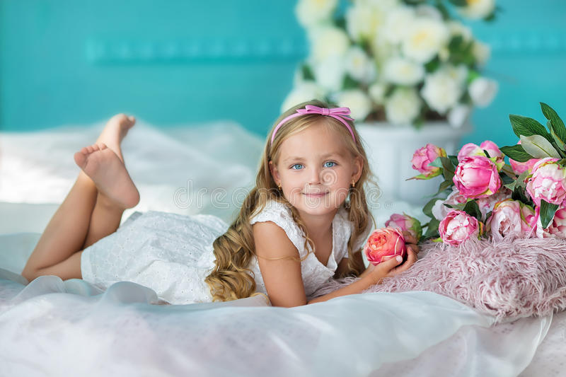 Trevlig seende ung flickadam i gulligt klänningsammanträde på en soffa med blommor i den vita stilfulla klänningen arkivbild