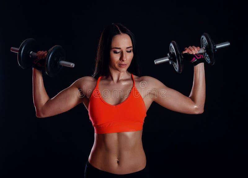 Trevlig sexig flicka som gör genomkörare med hantlar som isoleras över svart bakgrund Den idrotts- unga kvinnan gör en konditiong royaltyfria bilder