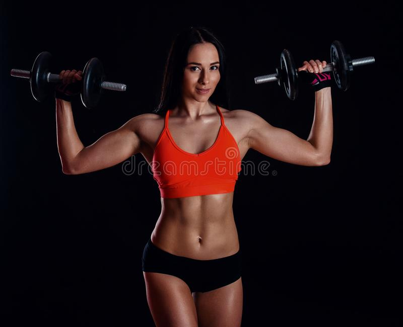 Trevlig sexig flicka som gör genomkörare med hantlar som isoleras över svart bakgrund Den idrotts- unga kvinnan gör en konditiong arkivfoton