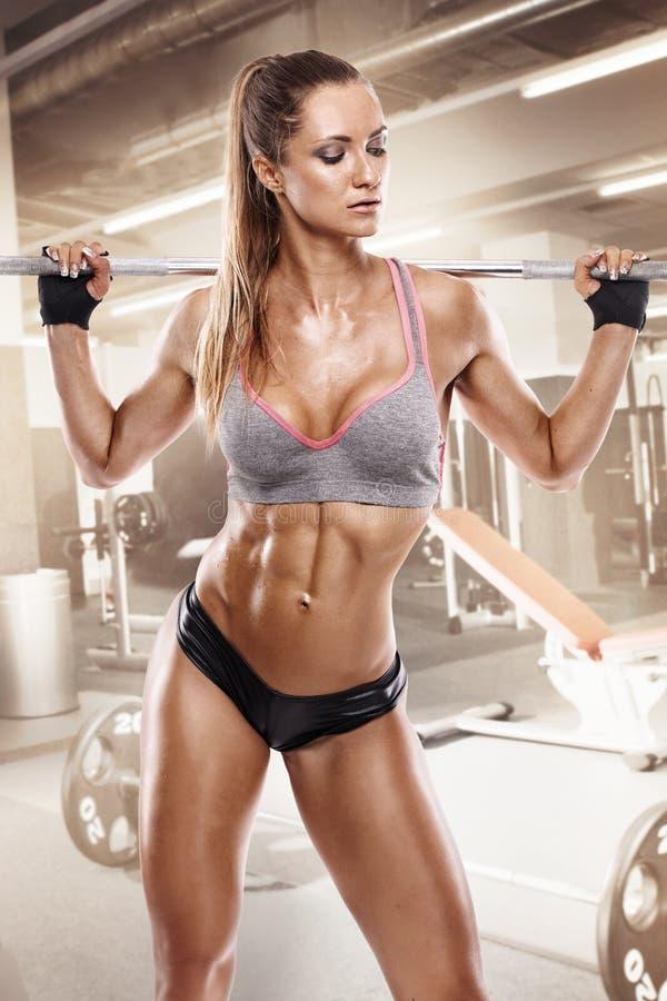 Trevlig sexig kvinna som gör genomkörare med den stora hanteln i idrottshallen, retouche royaltyfria foton