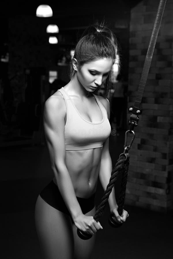 Trevlig sexig kvinna som gör tricepsgenomkörare i idrottshall royaltyfria bilder