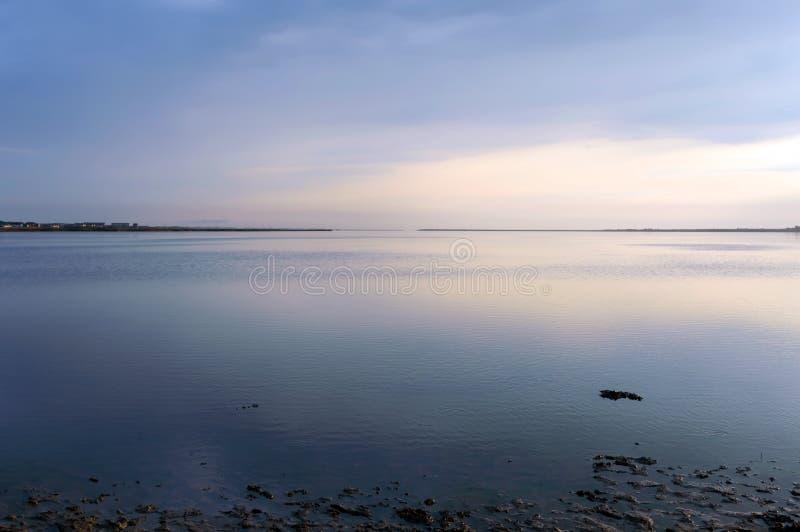 Trevlig sikt av breda flodmynningen över havssolnedgång Yttersida för lugna hav fotografering för bildbyråer